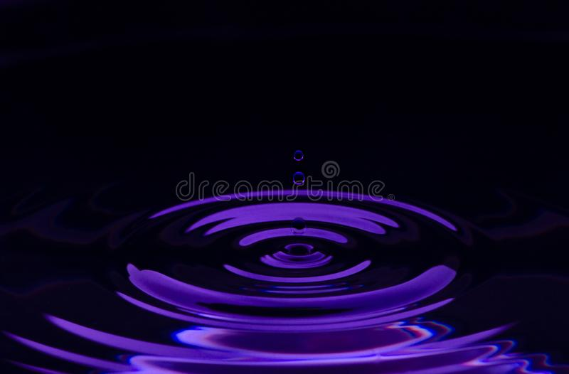 Water drop splash with purple colored stock photography