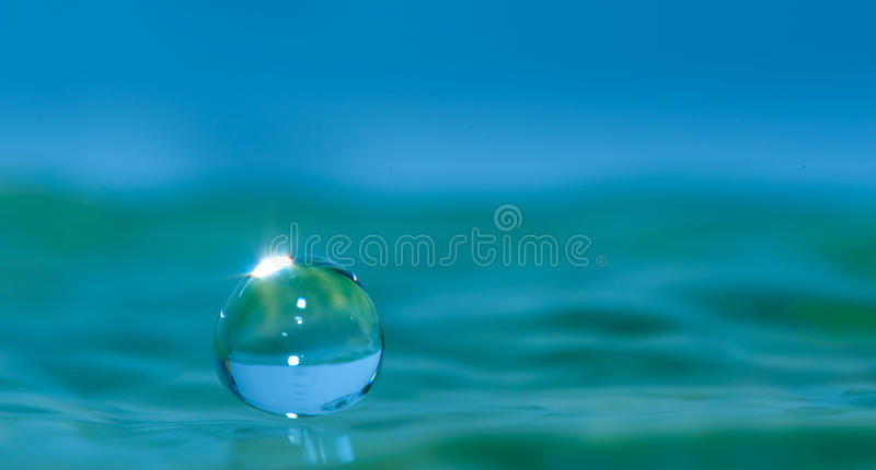 Water droplet. Macro shot of a water droplet impacting on liquid surface royalty free stock images