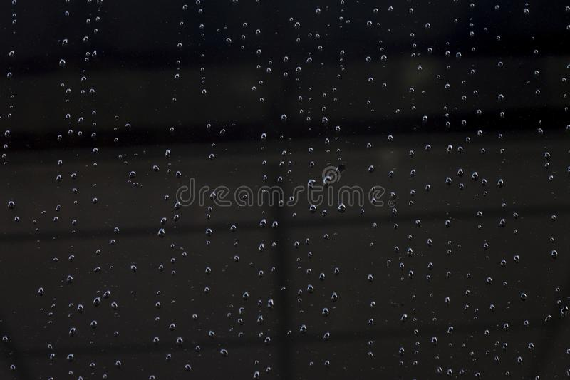 Water droplets flow on black glass. Water droplets flow on black glass for background and texture stock photo