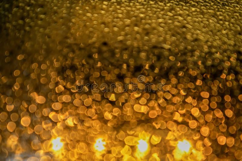 water droplets with golden light like beer glitter bokeh background stock image