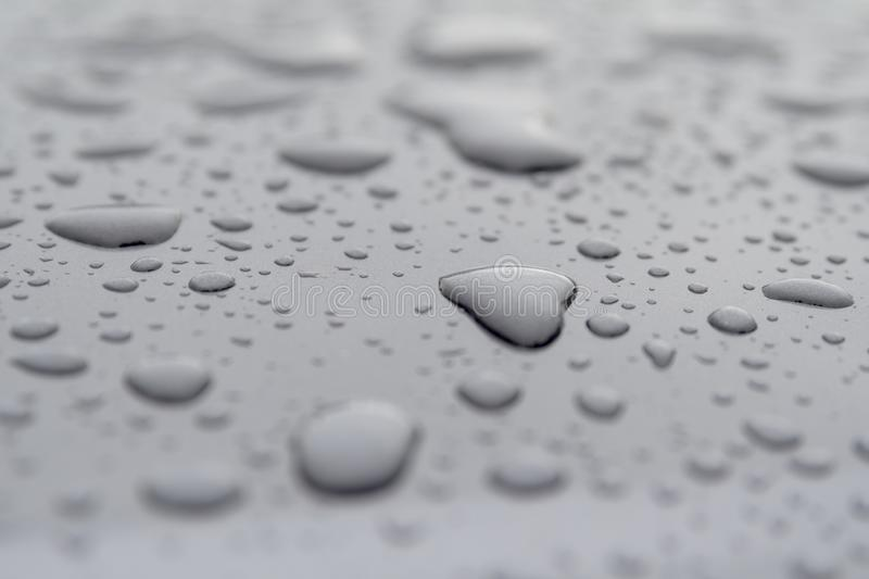 Inspirational heart shaped rain water drop on gray surface. Water droplets of rain on wet surface . love the rain when it falls. clean water supply comes from royalty free stock photo