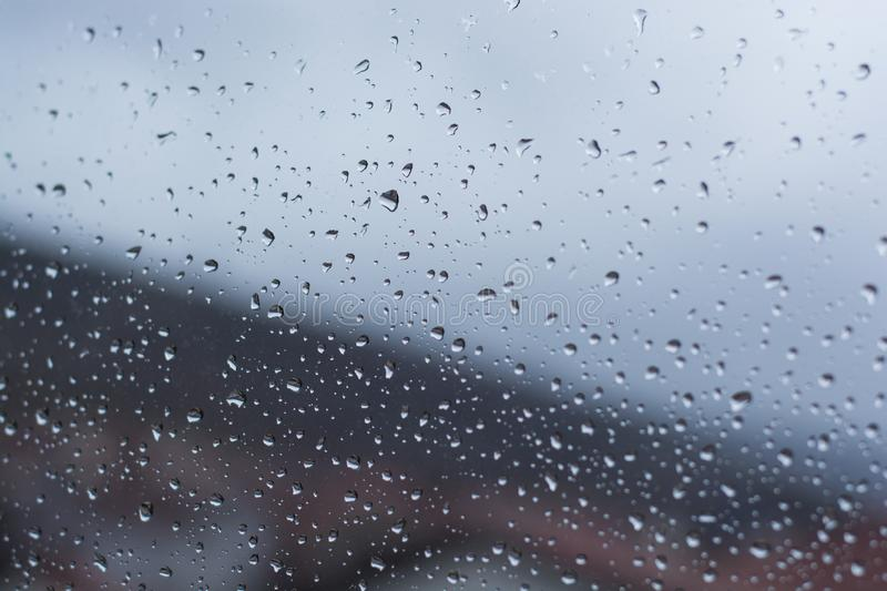 Water droplets on rainy window. Water droplets on windows at winter with strong out of focus background. Closeup image stock images