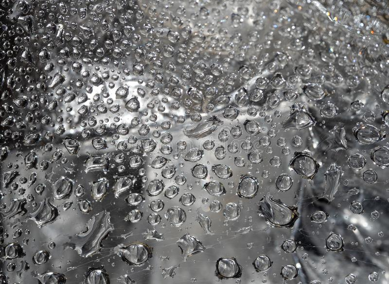 Water Droplets on a Spider Web Against a Silver Background. Water droplets caught on a spider web against a gray or silver background in a abstract pattern stock image