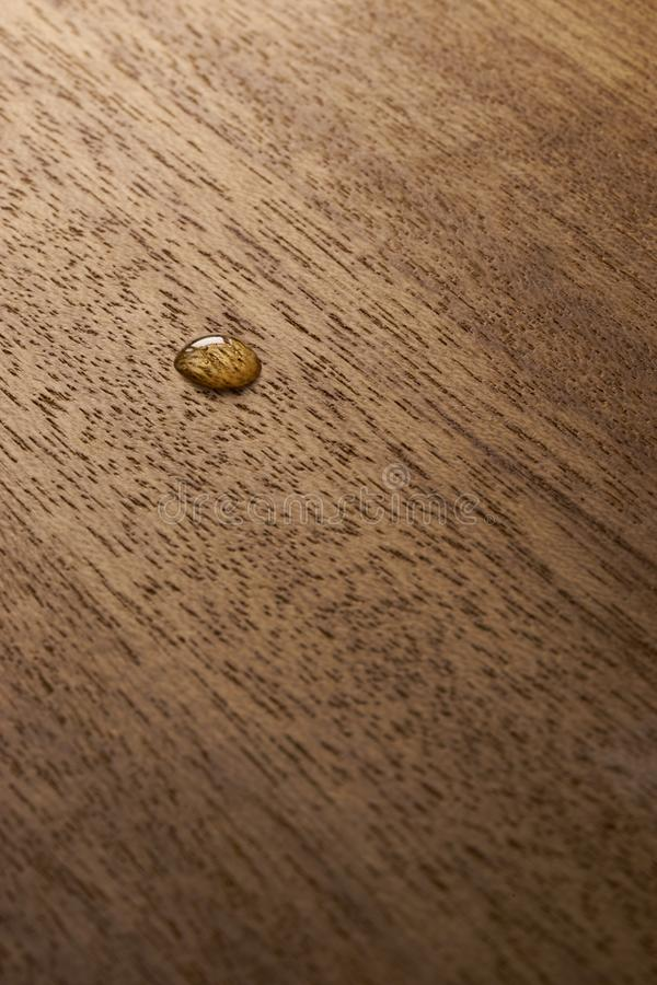 Water droplets on a wooden surface. Water drop on a wooden surface backgtound texture royalty free stock photos