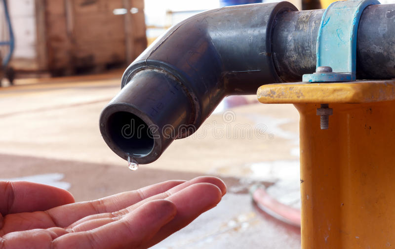 Water dropping from tap to hand someone. Water is dropping from tap to hand someone royalty free stock images