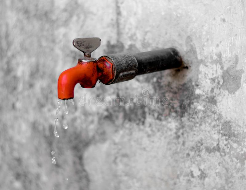 Water drops falling from a red colored tap in rural area. High shutterspeed royalty free stock photo