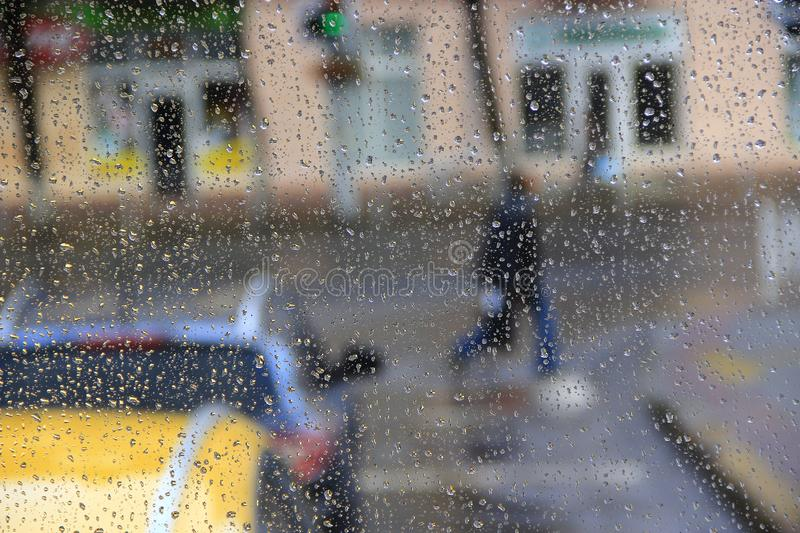 Water drops on glass during raining. Passers-by pass street in rain. Rain outside window on background of city life. Drops of water dropping on glass during rain royalty free stock photography