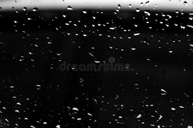 Water drops on glass texture abstract black dark background stock photo