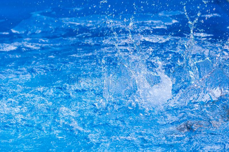Water drops over swimming pool, blue background with copy space stock photography