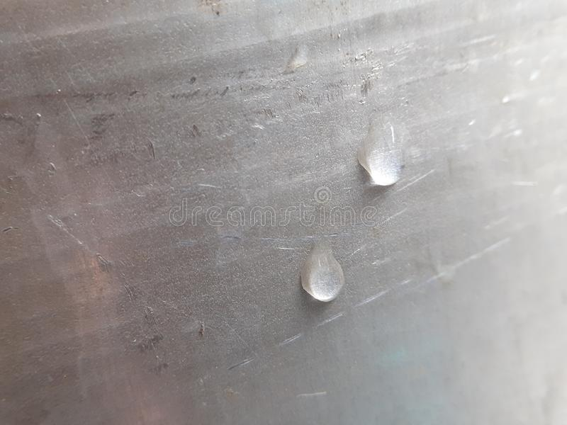 Water drops on a silver bucket. Texture of water drops on a silver bucket. Closeup metal image stock images
