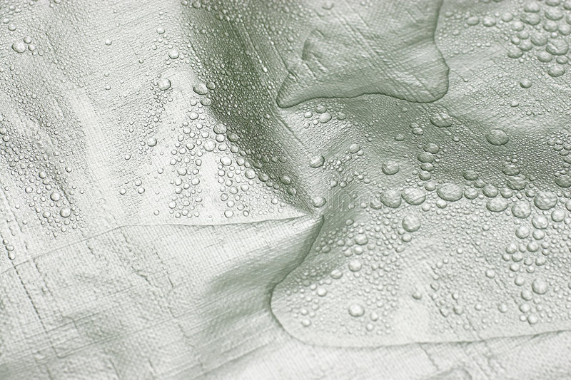 Water Drops on Silver Tarp. Water droplets naturally pooled on a bright silver construction tarp. Tarp has a textured pattern and rain drops add to the effect royalty free stock images