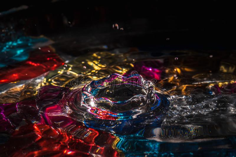 Water drops splash forming ripples and waves and abstract water columns in a colorful background royalty free stock photo