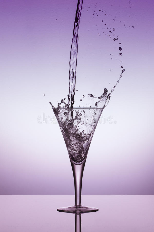 Water fall into a glass and splash on a purple background. Water fall into a glass and splash on a bright purple background stock photo