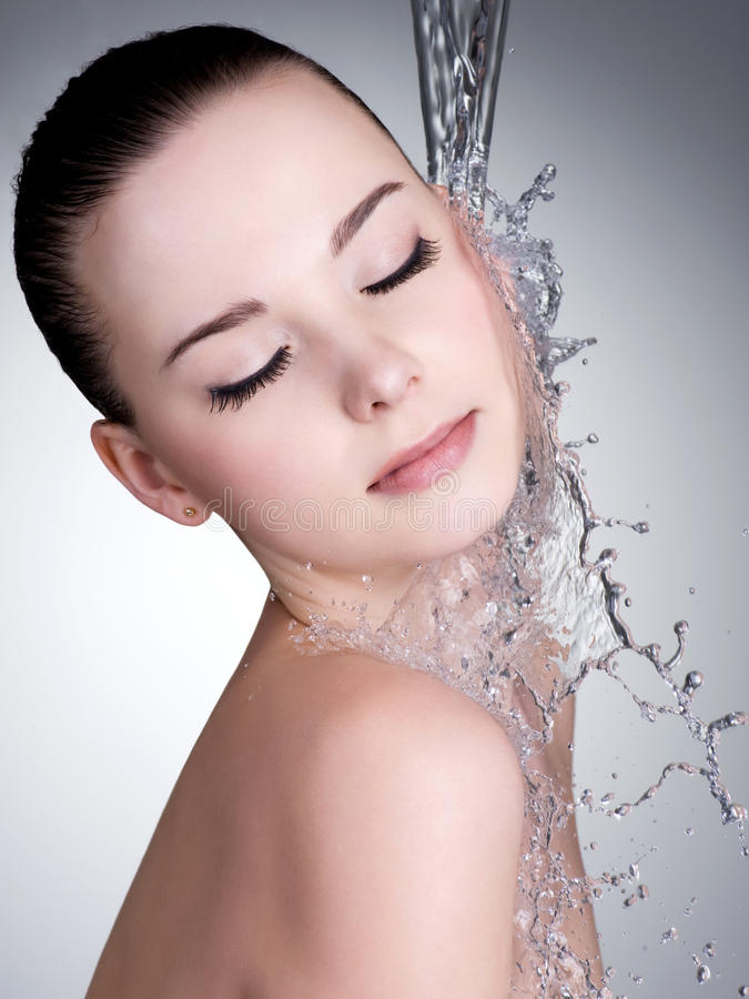 Water falling on the calm face of woman royalty free stock photography