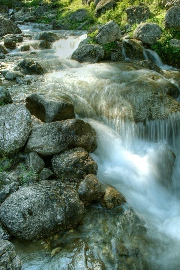 Water falling through mountain rocks. Picturesque scenery - water falling through mountain rocks royalty free stock photos