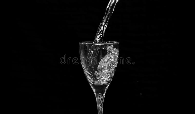 Water falling into a wine glass with a splash. Having a black background stock image