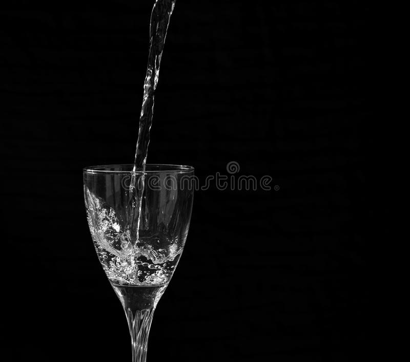 Water falling into a wine glass with a splash. Having a black background stock images
