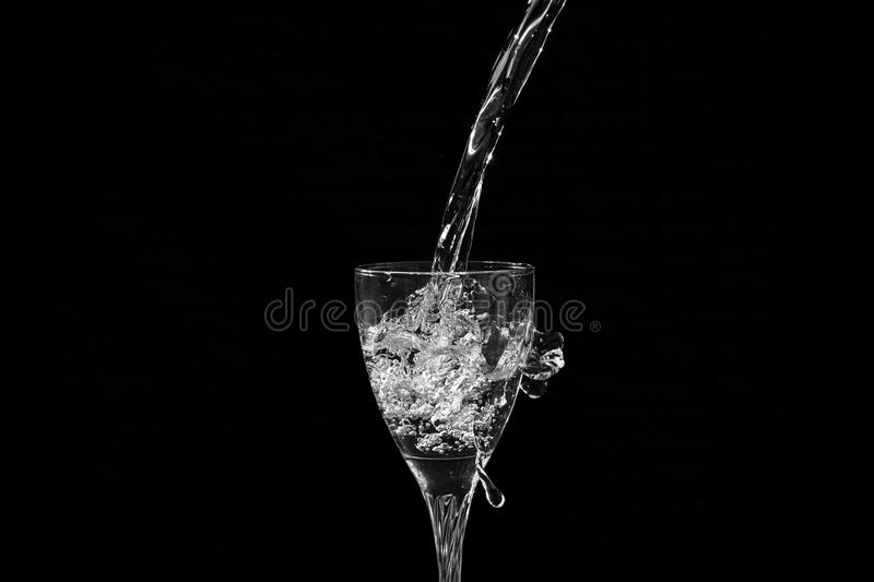 Water falling into a wine glass with a splash. Having a black background royalty free stock images