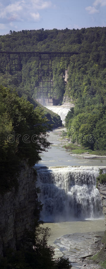 Water falls in upstate new york. An old railway bridge crosses a water fall in a state park in upstate new york stock images