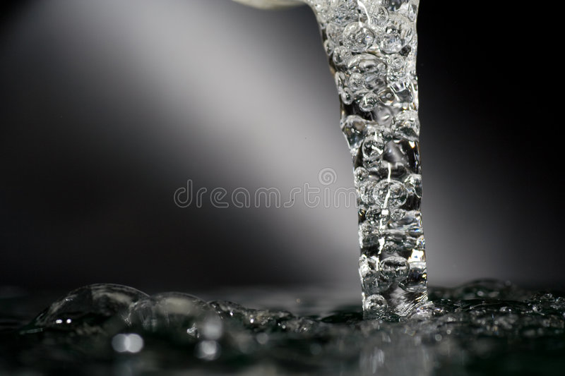 Water faucet. Water pouring out of a faucet with an aerator royalty free stock photography