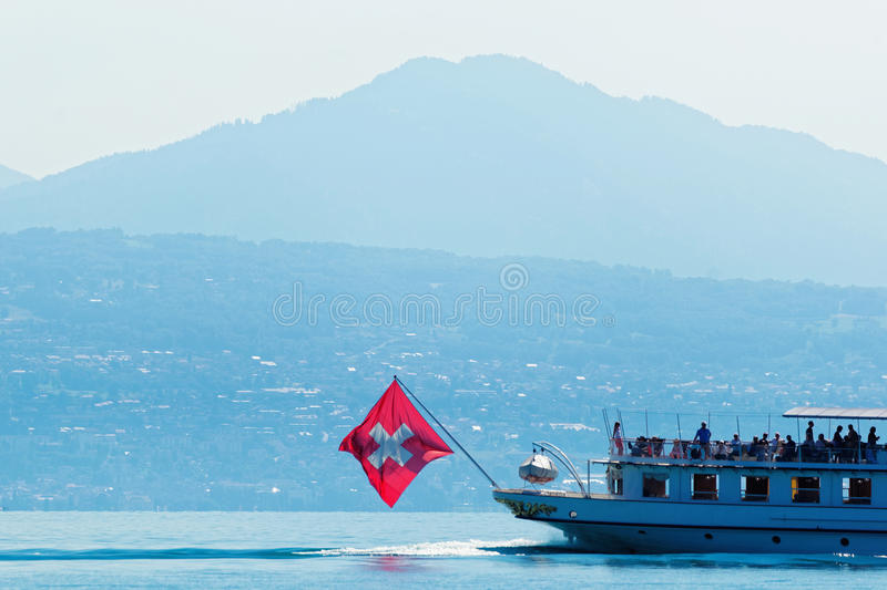 Water ferry with Swiss flag on Lake Geneva on Lausanne. Water ferry with Swiss flag in Lake Geneva at Ouchy embankment in Lausanne, Switzerland. People aboard royalty free stock photography