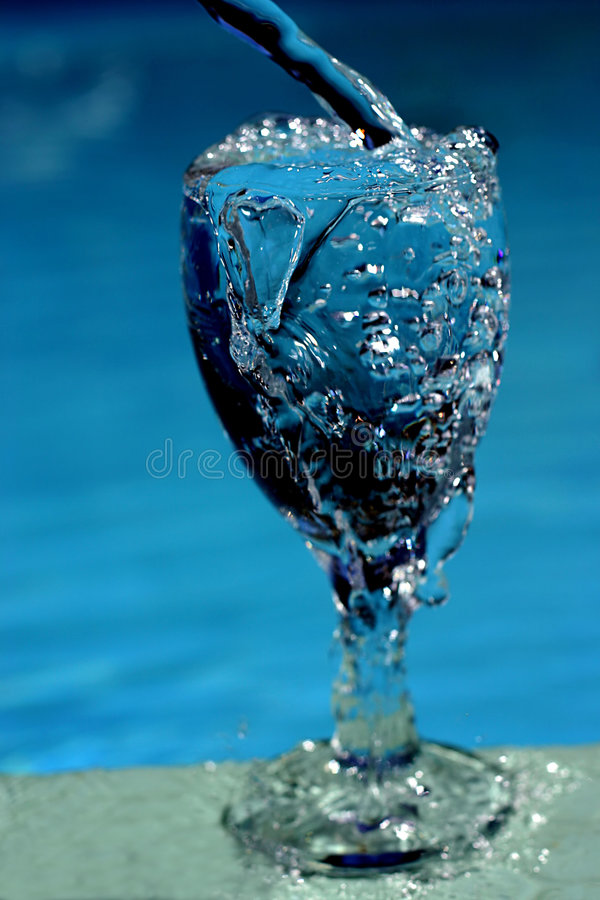 Water filling glass stock image