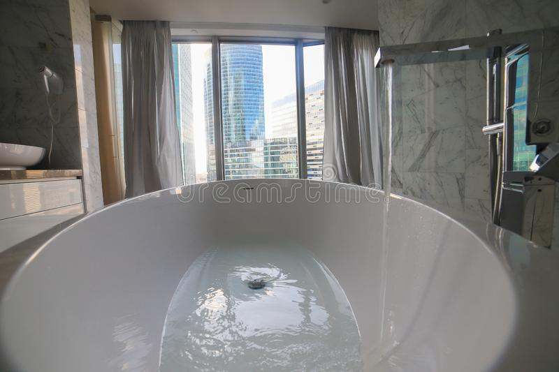 Water filling in modern bathtub in bathroom interior - modern glass buildings on a background stock images