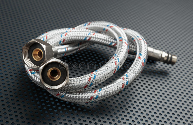 Water flexible hose in metallic braiding royalty free stock image