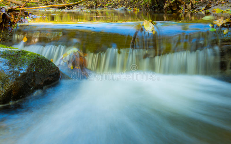 Water flow, fall leaves. Water flow in long exposure, fall leaves stock photo