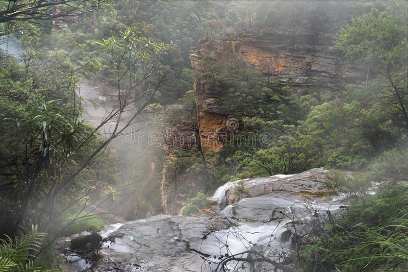 Water flow over the ledge at misty Wentworth Falls. Water fed by the Jamison Creek flows over the cliff edge at Wentworth Falls drop 187 metres to the bottom of royalty free stock photos