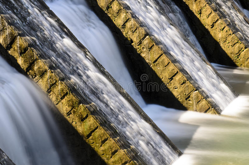 Water Flowing Detail. Water flowing on an old water reservoir built on a river, about 200 hundreds years old, to store water for a village and for agriculture stock photography