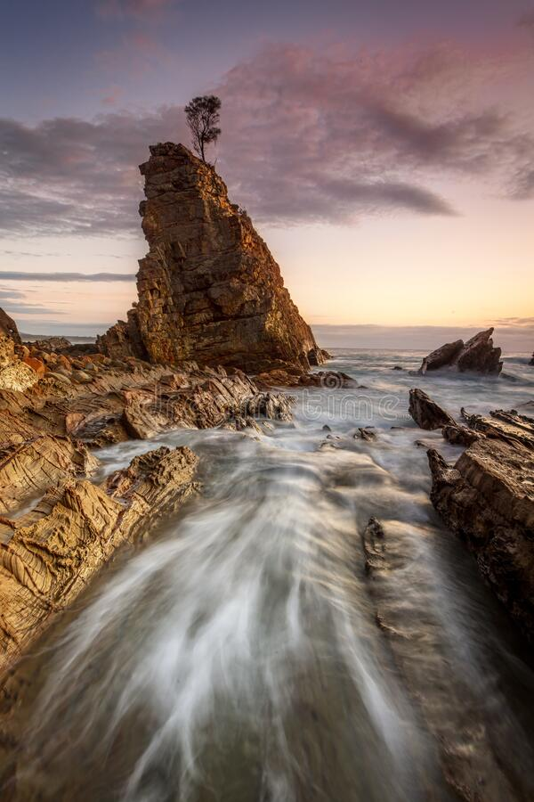 Water flowing fast through narrow chasm beside seastack woth sol stock photo