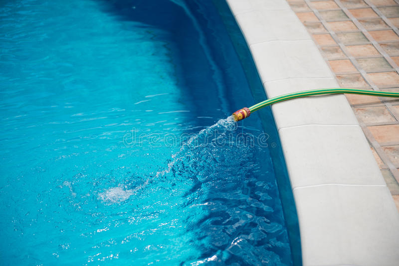 Water flowing from the hose into the pool, filling, servicing. Tube stock images