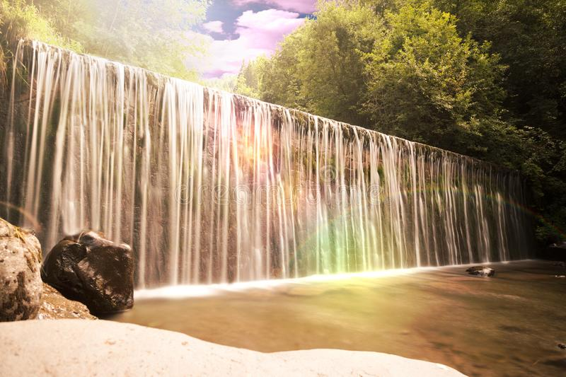 Water flowing over a ledge or dam wall. In a picturesque cascade or waterfall with lush green foliage and sun flare with rainbow at sunset royalty free stock photos