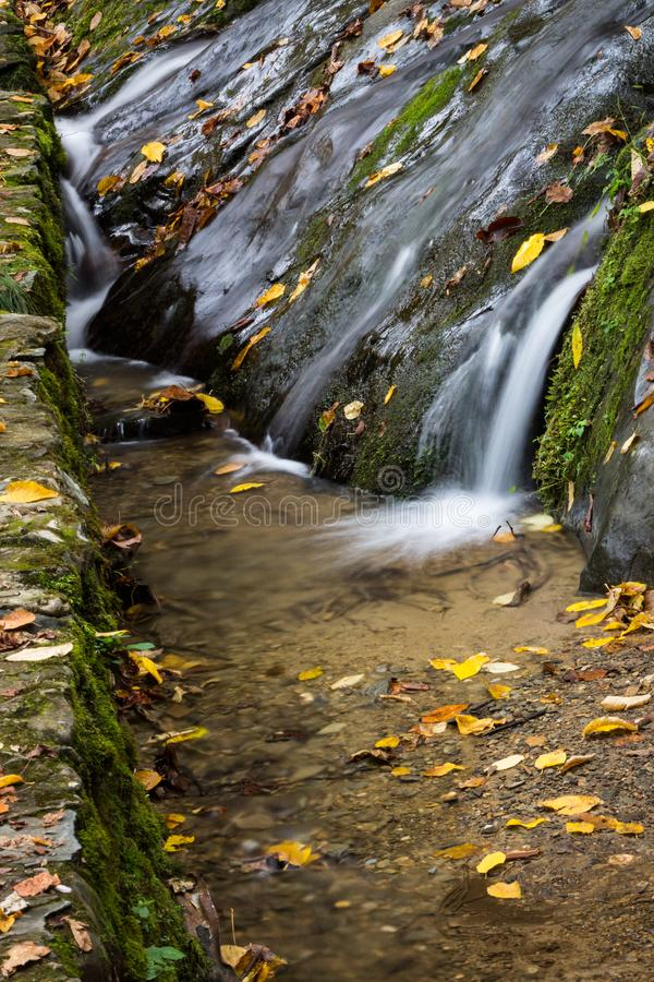 Water flowing over rocks into spillway, autumn season with fall leaves. Vertical aspect stock photos