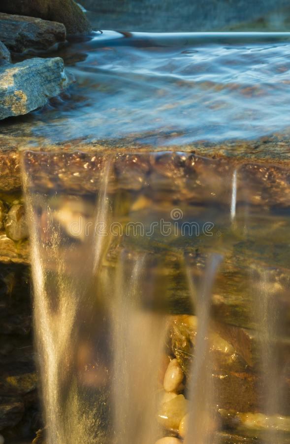 Water flowing from a pool. Waterfall running at sunset with water coming from a blue pool above royalty free stock photos