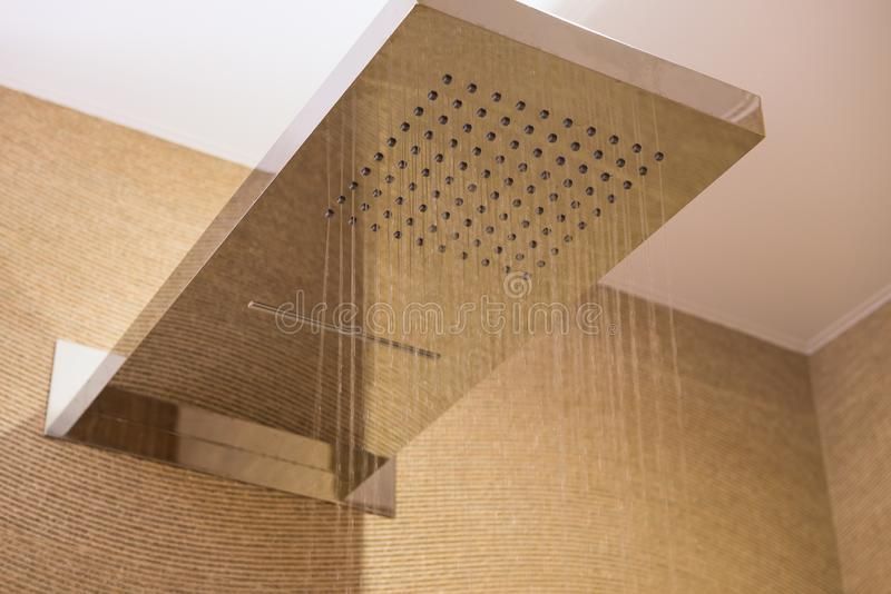 Water flowing from shower in beige bathroom interior, selective focus.  stock photos