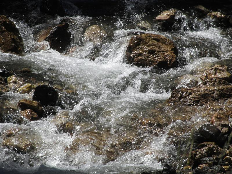 Water flowing and splashing over rocks in a mountain river stream.  royalty free stock photography