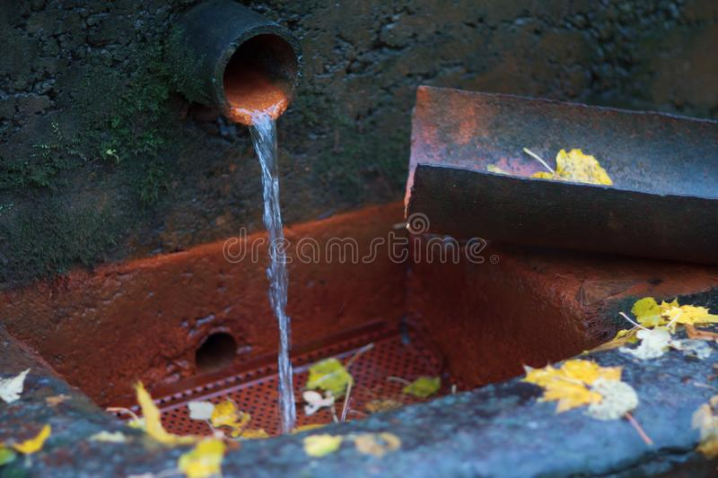 Water flows from the drainpipe to the drain stock photos