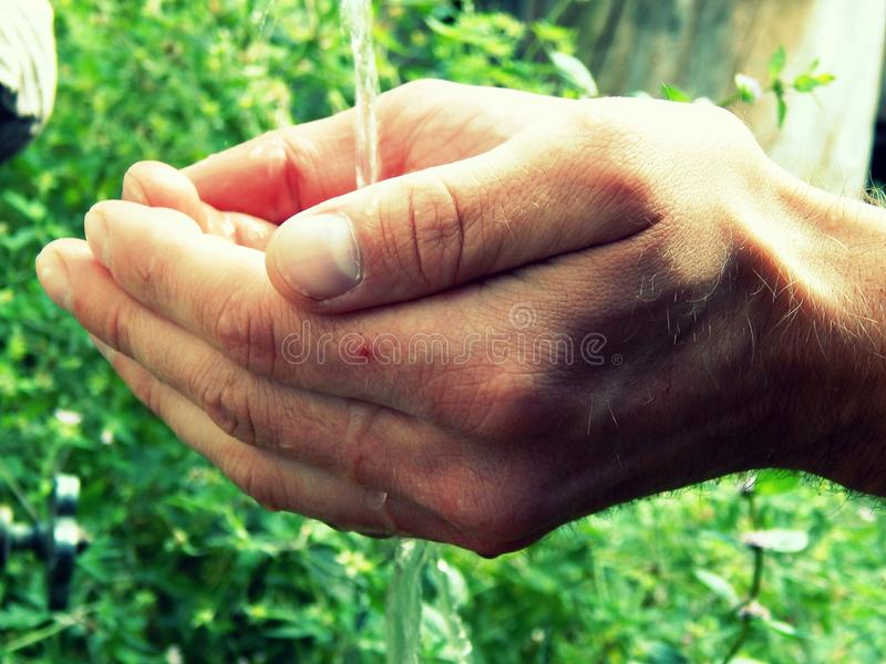 Water flows through the hands stock photography