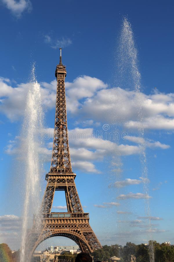 Water of Fountain and the Big Eiffel Tower. On the blue sky with clouds stock images