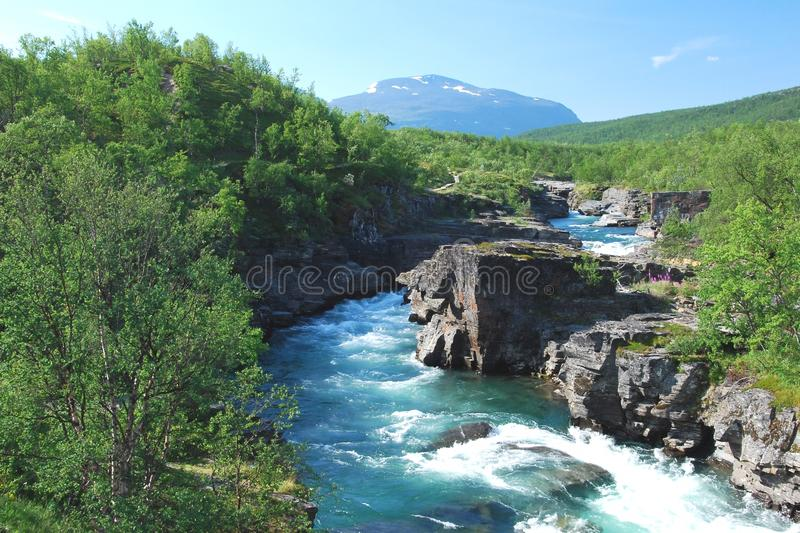 Water gear Abisko National Park Swedish Lapland. Fast flowing water gear Abisko National Park with rocky carved riverbed, forests and mountains - Kiruna royalty free stock photos