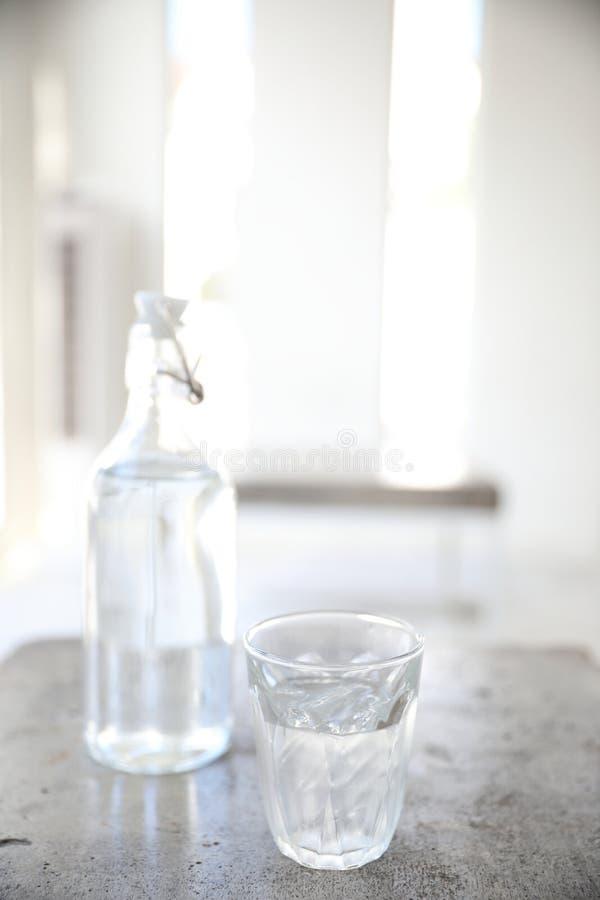 Water in glas en fles op lijst in koffiewinkel stock afbeelding