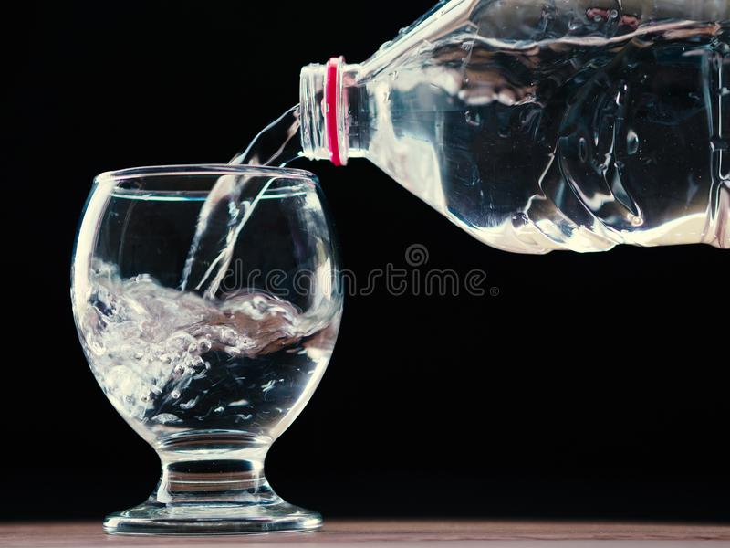 Water glass and water bottle with water filling and black background stock image