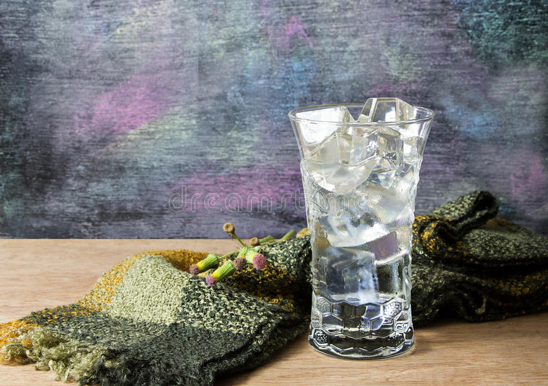 Water in a glass with ice placed on wooden table and blackboard royalty free stock image