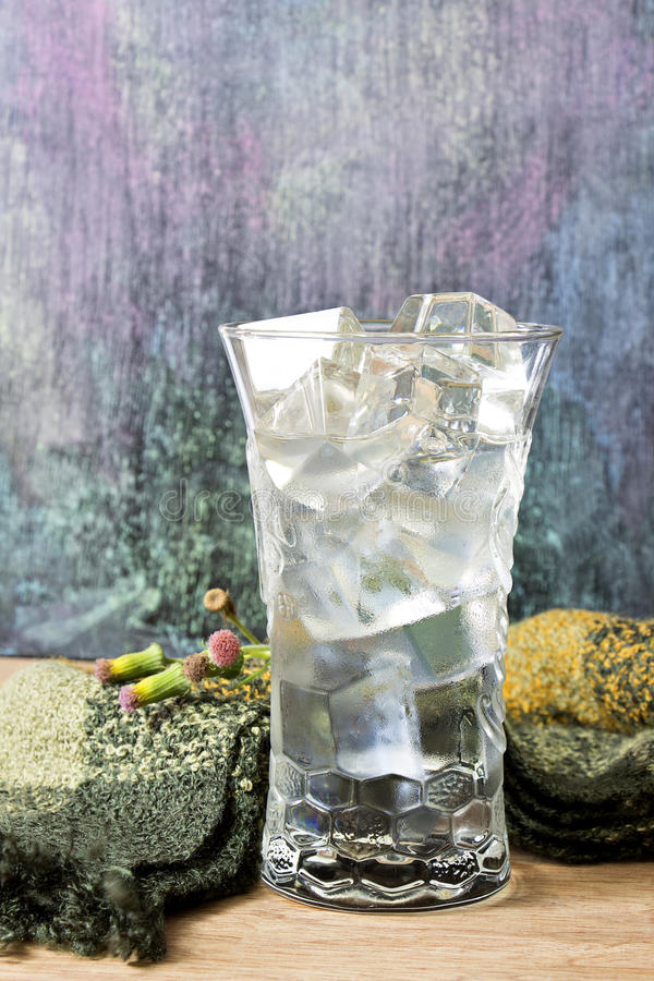 Water in a glass with ice placed on wooden table and blackboard royalty free stock photography