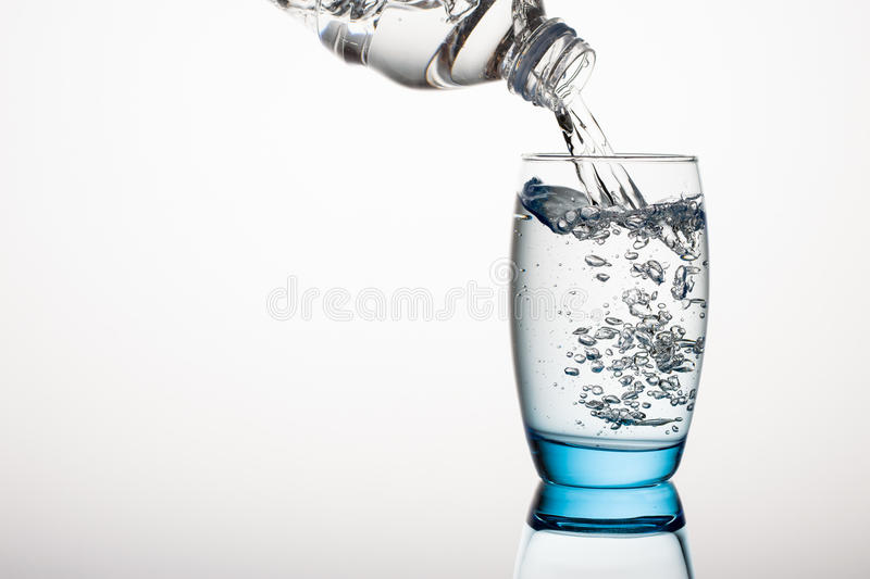 Water Glass. Pouring Water in Wateglasses on Gray Background royalty free stock photo