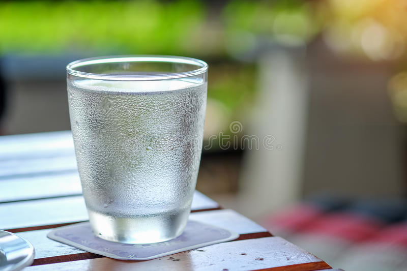 Water glass on wooden table. Water glass on wooden table with blurred background stock images