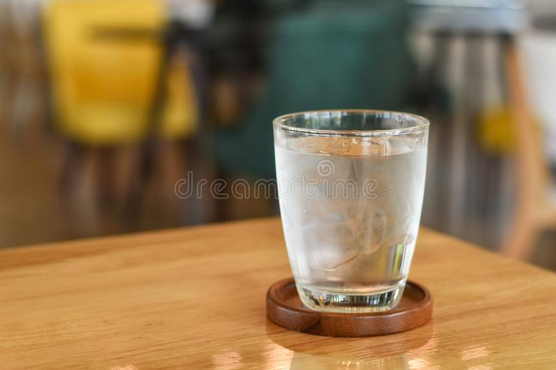 Water in a glass on wooden table. Drink, clear, clean, elements, simple, top, beverage, liquid, cool, cold, light, shadow, new, one, single, fresh, bright royalty free stock photography