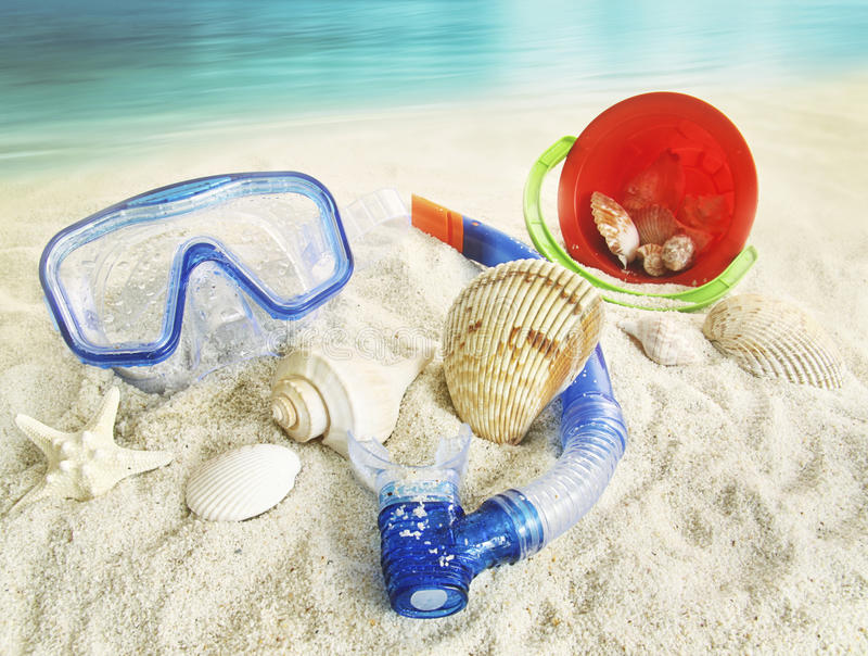Water goggles and toys in the sand. Water goggles and beach toys in the sand stock images